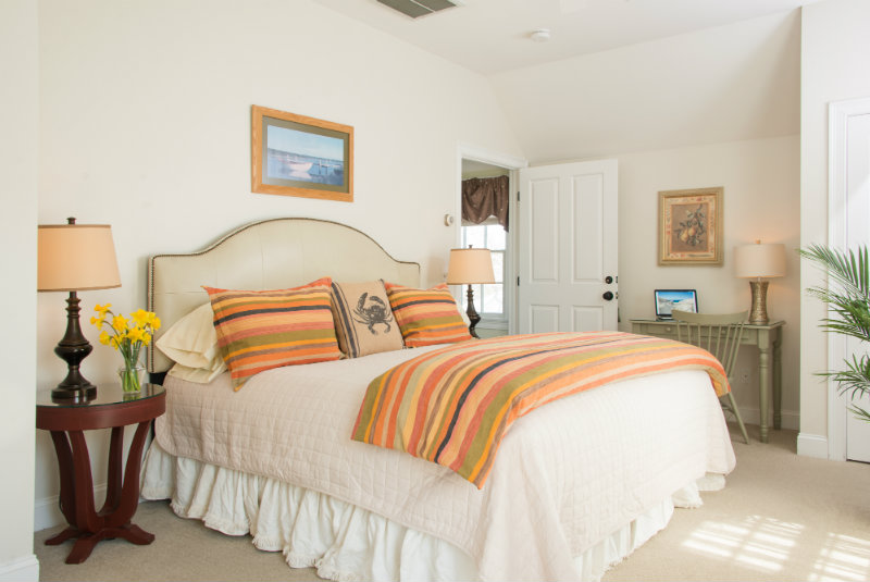Vaulted light-filled guest room with large bed and pastel bedding | Brewster By the Sea Cape Cod Inn | Brewster, MA
