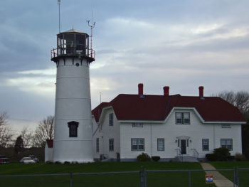 White lighthouse with red roof and attached house on an overcast day | Brewster By the Sea Cape Cod Inn | Brewster, MA