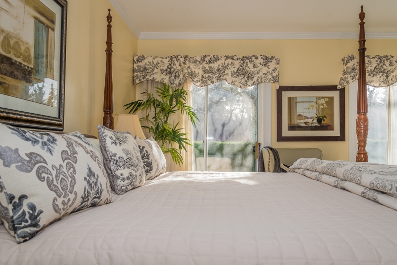 Soft yellow room with large, cozy four poster bed with white comforter | Brewster By the Sea Cape Cod Inn | Brewster, MA