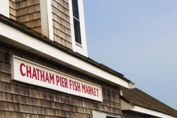 Chatham Fish Pier Market sign on the top of the building with blue sky in the background | Brewster By the Sea Cape Cod Inn | Brewster, MA