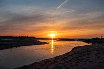 Sun setting over Paine's Creek with a person standing on the jetty | Brewster By the Sea Cape Cod Inn | Brewster, MA