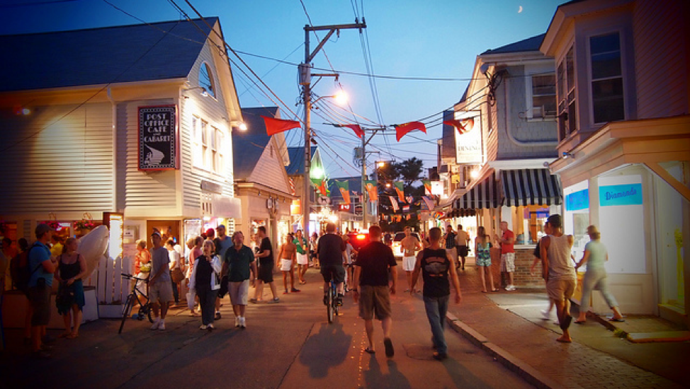 Crowd of people downtown at dusk walking down the street and in and out of shops | Brewster By the Sea Cape Cod Inn | Brewster, MA