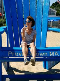 Brown haired woman sitting in an oversized bright blue rocking chair on a sandy beach | Brewster By the Sea Cape Cod Inn | Brewster, MA