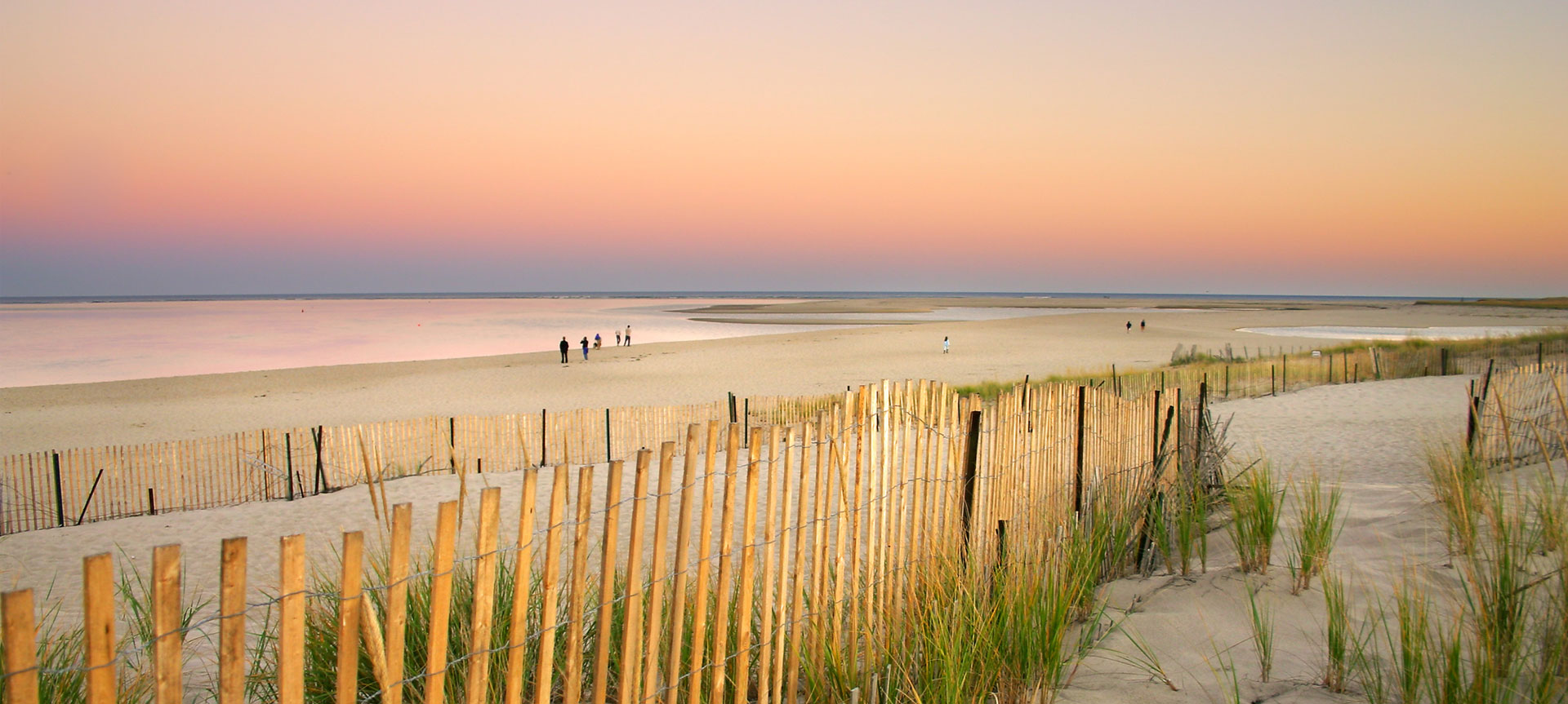 Beautiful sunset on the beach with sea grass and a fence in the foreground | Brewster By the Sea Cape Cod Inn | Brewster, MA
