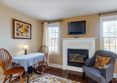Beach Blossom Fireplace Bed with Chairs | Brewster By the Sea Cape Cod B&B | Brewster, MA